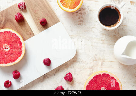 Close up of breakfast table with fresh coffee, grapefruit, oranges and raspberries. - Stock Image