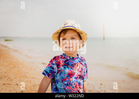 A portrait of a boy wearing summer clothing and a summer hat at the seaside - Stock Image