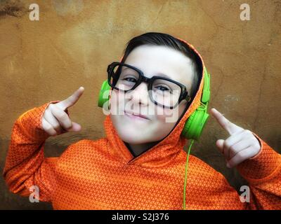 Happy and young boy with black glasses listening to music on stereo headphones - Stock Image
