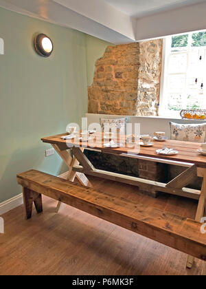 Wooden trestle table set with china cups, saucers, plates and cutlery ready for serving afternoon tea in Kavanagh's Tea Rooms Oakham, Rutland, UK - Stock Image
