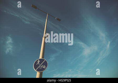 Wide angle shot of street pole with blue road sign 'bicycle and pedestrian lane' on it, sunny summer day - Stock Image
