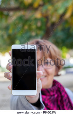 A woman holds a white mobile phone with the empty screen in a vertical position in an external location. - Stock Image