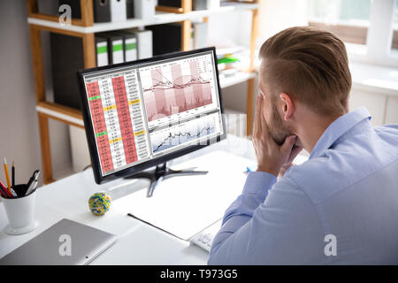 Despairing businessman faced with financial losses sitting at his desk consulting graphs on monitors - Stock Image