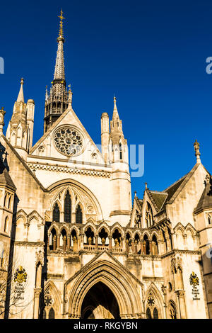Winter sunlight on the main entrance and spire of the Royal Courts of Justice, The Strand, London, UK - Stock Image