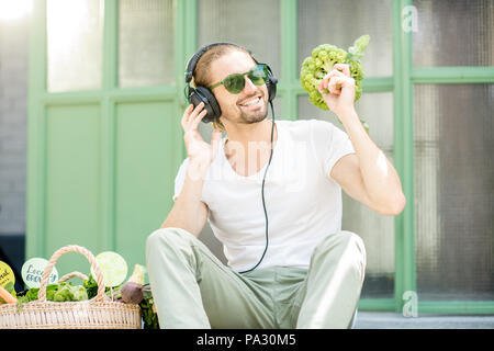 Funny portrait of a man listening to the music shaking with broccoli outdoors on the green background - Stock Image