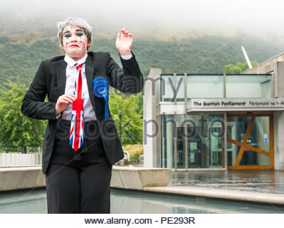 Edinburgh, Scotland, UK. 12th August 2018. Edinburgh Fringe Festival Photocall on a dreary Scottish weather day, Scottish Parliament, Holyrood, Edinburgh, Scotland, United Kingdom. Political clowns in silly poses outside the parliament. Pig Circus is billed as a 'Verbatim Brexit parody' about the government's handling of Brexit negotiations, with character Teresa May standing in front of the Scottish Parliament building. Produced by theatre group Hitchhiker Collective - Stock Image