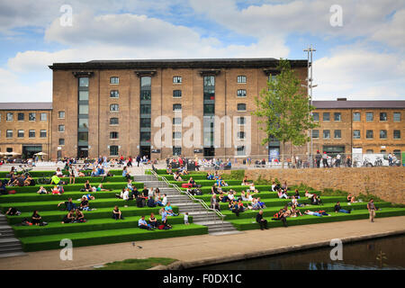 Students sitting on steps alongside the Regent's Canal in front of Central Saint Martins - Stock Image