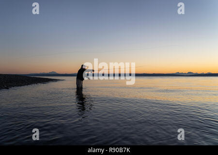 A silhouette view of a fly fisherman casting for salmon and searun coastal cutthroat trout from a salt water beach at a beach on the north west coastl - Stock Image