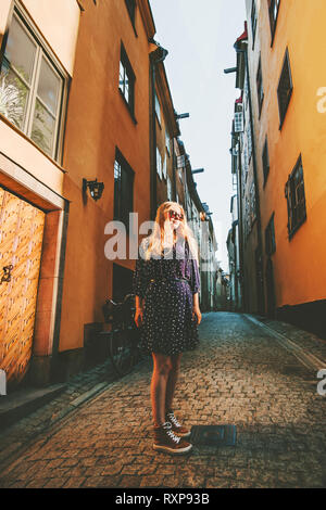 City walk in Stockholm woman traveling alone fashion lifestyle summer vacations in Sweden old city cobblestone street - Stock Image
