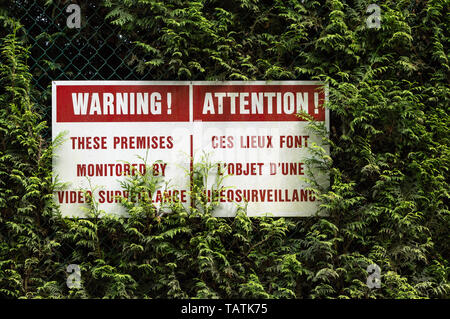 Bi-lingual English and French language surveillance warning sign with red lettering hung on chain link fence in green cedar hedge. - Stock Image