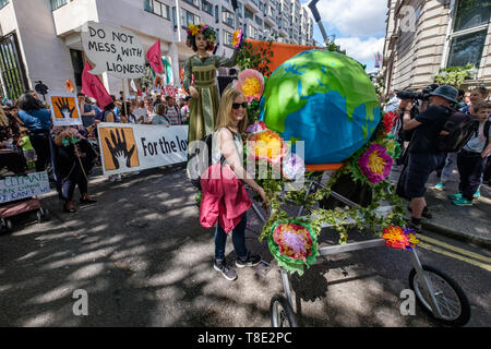 London, UK. 12th May 2019. One of the giant pushchairs carrying a globe which followed behind 11-year-olds at the front of the Mothers Day March by thousands from Hyde Park Corner to a rally filling Parliament Square, backing Extinction Rebellion's call for the drastic and urgent action needed to avert the worst consequences of climate change, including possible human extinction. Our politicians have declared a climate emergency but now need to take real action rather than continuing business as usual which is destroying life on our planet. Peter Marshall/Alamy Live News - Stock Image