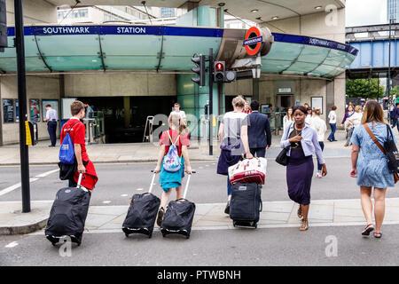 London England United Kingdom Great Britain Southwark street crossing woman boy girl teen family dragging rolling luggage Southwark Underground Statio - Stock Image