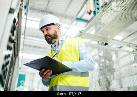A portrait of a mature industrial man engineer with clipboard in a factory, working. Copy space. - Stock Image