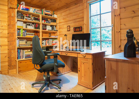 Black upholstered swivel office chair and wooden desk with computer, built-in wall bookcase  in home office set-up on ground floor rinside a piece sur piece Scots pine log home, Quebec, Canada. This image is property released. CUPR0334 - Stock Image