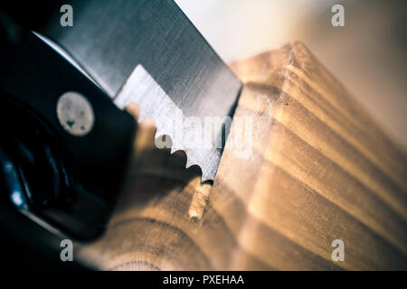 Macro Of A Jagged Steak Knife Partially Pulled Out Of A Kitchen Knive Block On A Table - Stock Image