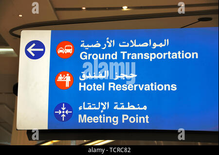Dubai, United Arab Emirates-February 07, 2014: Sign in English and Arab at Dubai airport indicating the way to the ground transportation, the hotel re - Stock Image