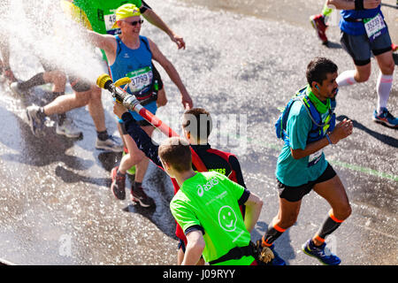Paris, France - April 09, 2017 : A french firefighter spray water on runners of Paris Marathon 2017 during this - Stock Image