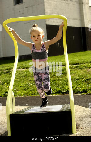 Six year old girl, on a running machine in a free to use outdoor fitness area - Stock Image