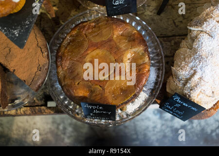 Baked goods and treats: An image of an apple and honey cake in among other cakes and tarts on display at a restaurant - Stock Image