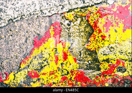 Red and yellow paint on a stone surface as an abstract texture - Stock Image