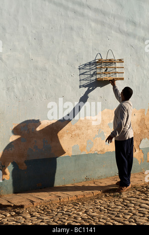 Cuban man hanging up a bird cage on a wall, Trinidad, Cuba. Keeping caged birds is commonplace in Cuba - Stock Image