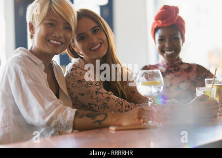 Portrait smiling young women friends drinking cocktails in bar - Stock Image