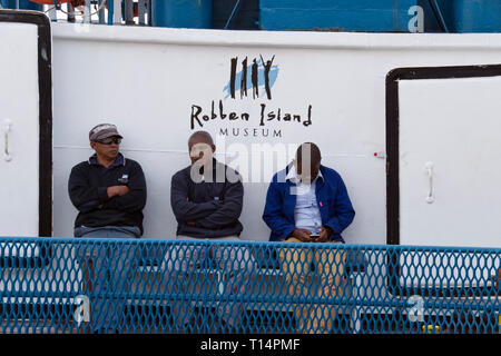 Robben Island employees on a ferry to the island where Nelson Mandela was imprisoned before the fall of apartheid, in Table Bay, Cape Town, South Afri - Stock Image