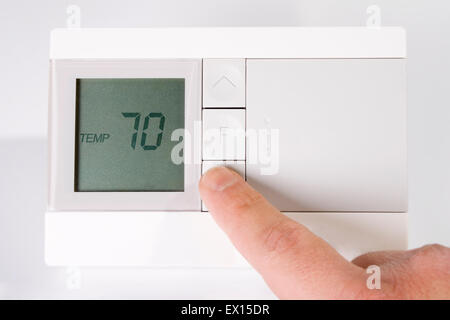 Stock image of hand adjusting thermostat - Stock Image