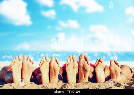 Group of friends having fun on the beach with their foots. Concept of summertime - Stock Image