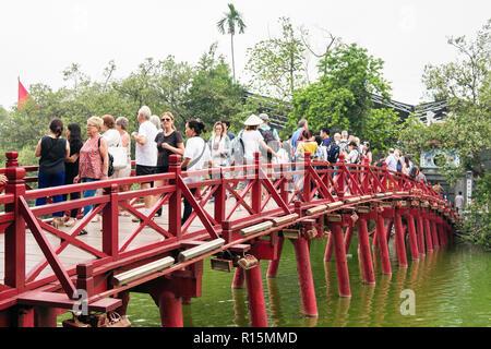 Tourists on wooden Red Huc bridge to Ngoc Son Temple in Hoan Kiem lake. Hanoi, Vietnam, Asia - Stock Image
