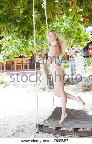 Young woman wearing white bikini standing on swing - Stock Image