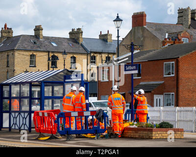 A gang of Railway Maintenance workers in orange overalls erecting new solar powered lights on the Platform at Saltburn North Yorkshire - Stock Image