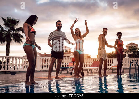 Group of happy friends dancing at pool party at sunset - Young millennial people having fun in a tropical luxury resort - Stock Image