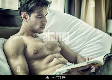 Sexy handsome young man laying shirtless on his bed next to window, reading a book - Stock Image