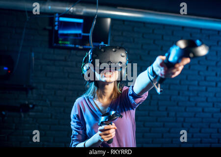 Young woman playing game using virtual reality headset and gamepads in the dark room of the playing club - Stock Image