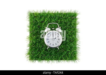 Old style alarm clock on square of green grass field isolated on white background with clipping path - Stock Image