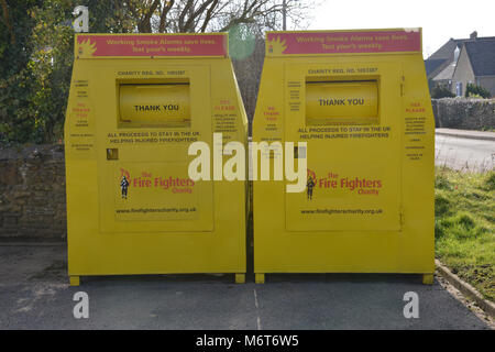 Fireman's Charity clothes bins outside the fire station in the north Oxfordshire village of Hook Norton - Stock Image