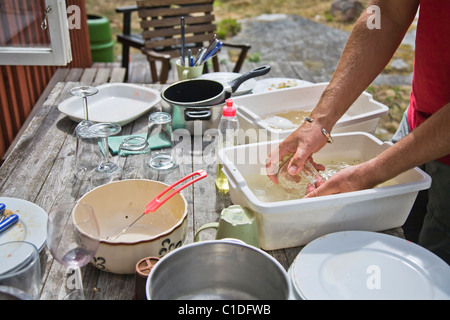 Man washing dishes outdoors in summer. - Stock Image