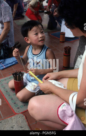 Mother and son at Ancestral Worship temple in Hong Kong preparing the incense - Stock Image