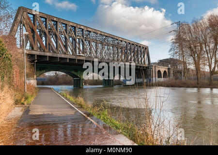 The 19th century cast iron railway bridge over the River Nene in central Peterborough which is still in use on the - Stock Image