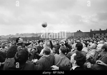 The traditional Royal Shrovetide Football Match, a 'medieval football' game played annually on Shrove Tuesday and Ash Wednesday in the town of Ashbourne in Derbyshire. Guest of honour Sir Stanley Matthews 'turns up' the ball to start the game for the villagers. 22nd February 1966. - Stock Image