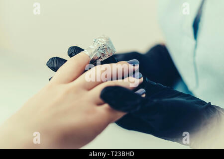 Soaking off gel manicure. - Stock Image