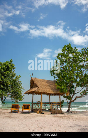 A paradise island beach shade hut and sun loungers on a white sand beach. - Stock Image