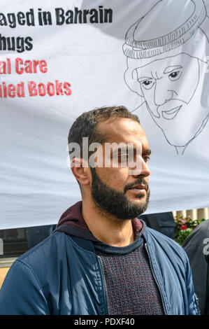 London, UK. 10th August 2018. Ali Mushaima who has been on hunger strike at the Bahrain embassy since the start of August to save his fathers life stands in front of a banner with a drawing of his father at the vigil by Inminds Islamic human rights organisation vigil calling for the immediate release of Hassan Mushaima and all the other 5000 Bahraini prisoners of conscience languishing in the Al-Khalifa regimes jails. They also demanded the British government end its complicity in the Al Khalifa dictatorship's crimes against the Bahraini people. Credit: Peter Marshall/Alamy Live News - Stock Image