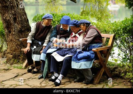 Naxi women absorbed in reading a book, Black Dragon Pool Park, Lijiang, Yunnan, China. - Stock Image