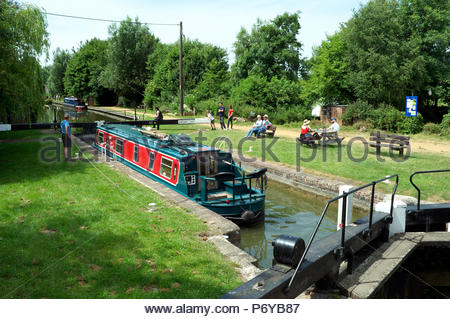 A narrow boat heads west at Kintbury Lock on the Kennet & Avon Canal, near Hungerford, Berkshire, UK. - Stock Image
