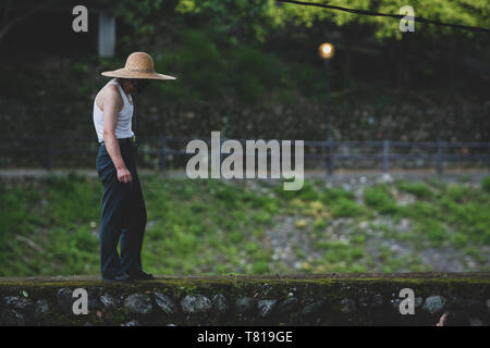 Hualien, Taiwan. 12th Jun, 2009. Daily life. Elderly man with a straw hat stands on top of old stone wall in Hualien, Taiwan. - Stock Image