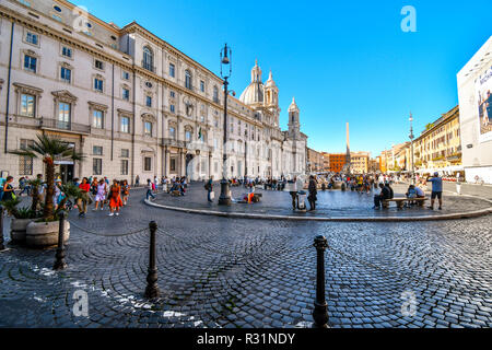 Tourists and locals enjoy a busy autumn morning inside the Piazza Navona in front of the Sant'Agnese in Agone Church in Rome, Italy. - Stock Image