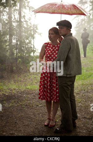 Young couple in rain under umbrella with vintage clothing - Stock Image