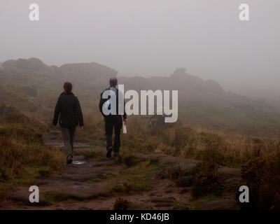 Middle aged couple hiking in the fog on The Roaches, The Peak District, Staffordshire, UK - Stock Image